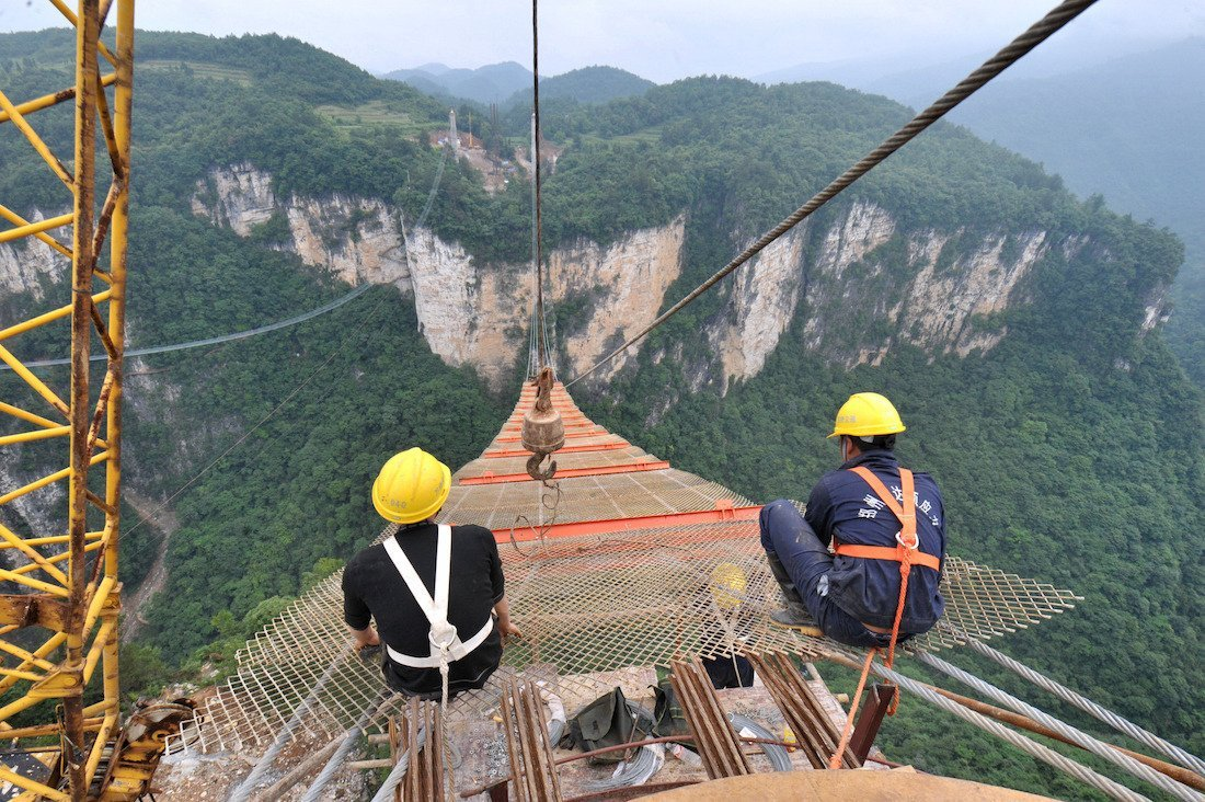 (Workers build the vitreous bridge above the grand canyon in Zhangjiajie, central China's Hunan Province, June 15, 2015.