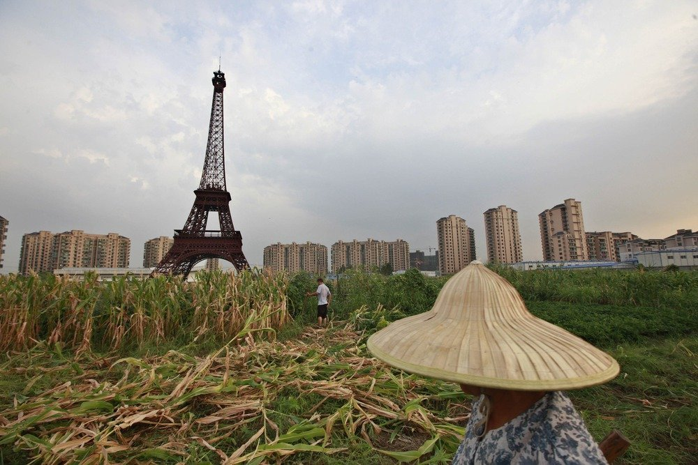 "A farmer walks through a field near a replica of the Eiffel Tower at the Tianducheng development in Hangzhou, Zhejiang Province August 1, 2013. Tianducheng, developed by Zhejiang Guangsha Co. Ltd., started constructing in 2007 and was known as a knockoff of Paris with a scaled-replica of the Eiffel Tower, standing 108 metres, and Parisian houses. Although designed to accommodate at least ten thousand people, Tianducheng remains sparsely populated and is now considered as a ""ghost town"", according to local media. REUTERS/Aly Song (CHINA - Tags: SOCIETY ENVIRONMENT BUSINESS REAL ESTATE TPX IMAGES OF THE DAY)"